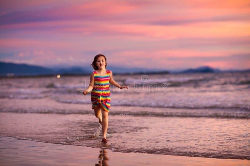 Ni?o que juega en la playa del oc?ano Ni?o en el mar de la puesta del sol fotos de archivo