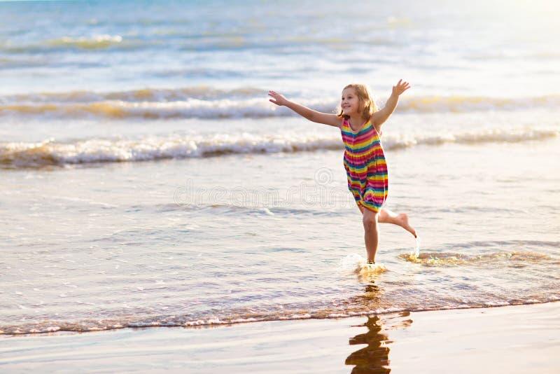 Ni?o que juega en la playa del oc?ano Ni?o en el mar de la puesta del sol imagenes de archivo