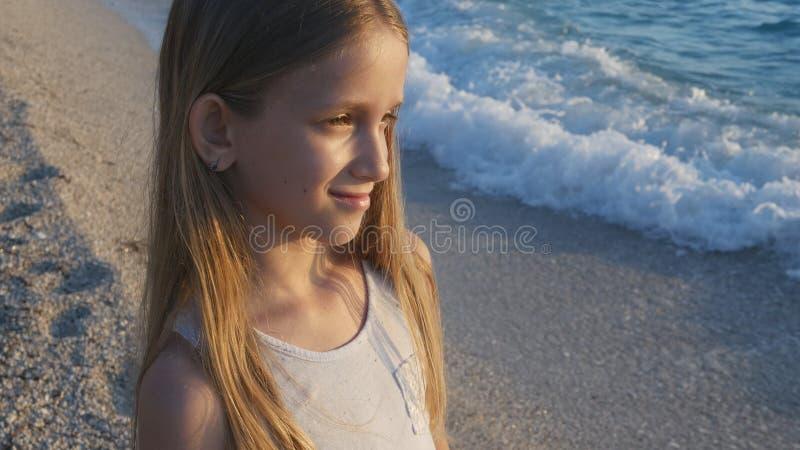 Ni?o que juega en la playa en puesta del sol, ondas de observaci?n del mar del ni?o, retrato de la muchacha en orilla fotografía de archivo