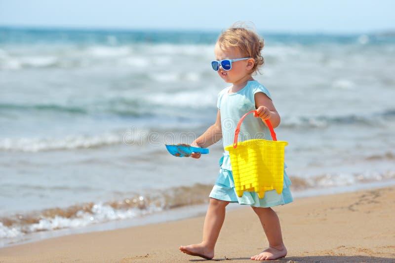 Ni?o que juega en la playa tropical Arena de excavaci?n de la ni?a en la orilla de mar Los niños juegan con los juguetes de la ar foto de archivo