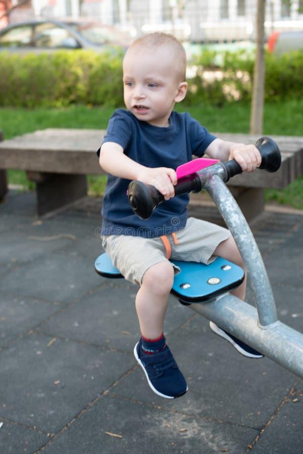 Ni?o que juega en patio al aire libre en verano Los ni?os juegan en yarda de la guarder?a Ni?o activo en el oscilaci?n colorido S foto de archivo
