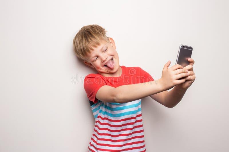 Ni?o que toma un selfie con el tel?fono celular aislado en el fondo blanco Retrato del estudio foto de archivo