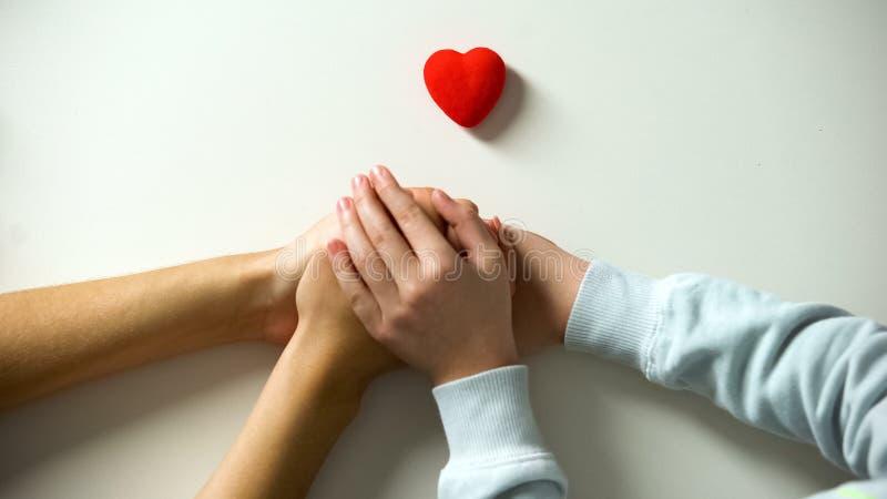 Ni?o y persona adulta que llevan a cabo las manos, muestra del coraz?n en el fondo blanco, custodia fotografía de archivo libre de regalías