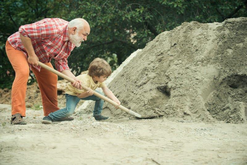 Ni?o y trabajos Poco trabajador del hijo con la pala Peque?o hijo que ayuda a su padre con el edificio a trabajar Concepto de la  fotos de archivo libres de regalías