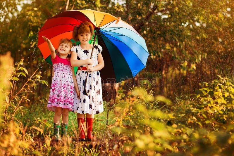 Ni?os con el paraguas colorido que juega en lluvia de la ducha del oto?o Las ni?as juegan en parque por el tiempo lluvioso imágenes de archivo libres de regalías