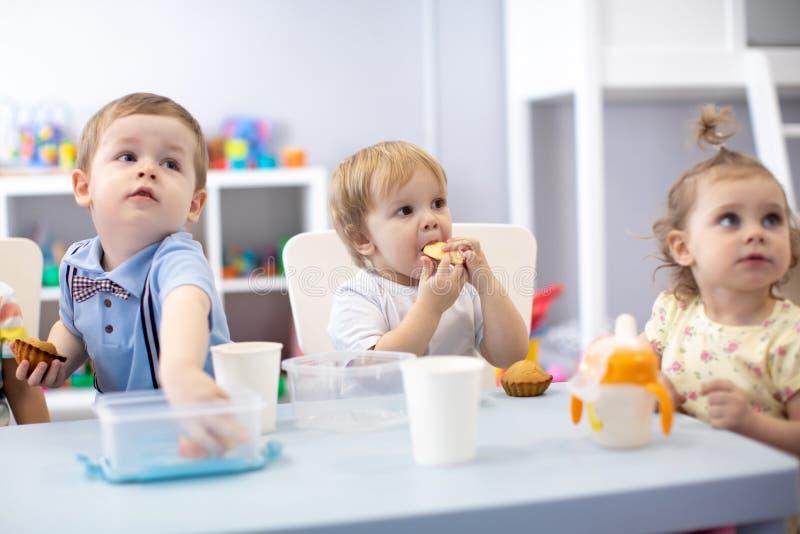 Ni?os de los beb?s que comen la comida sana en cuarto de ni?os o guarder?a fotografía de archivo