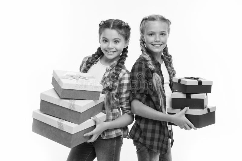 Ni?os emocionados sobre el desempaque de los regalos Las peque?as hermanas de las muchachas recibieron los regalos de cumplea?os  imagenes de archivo