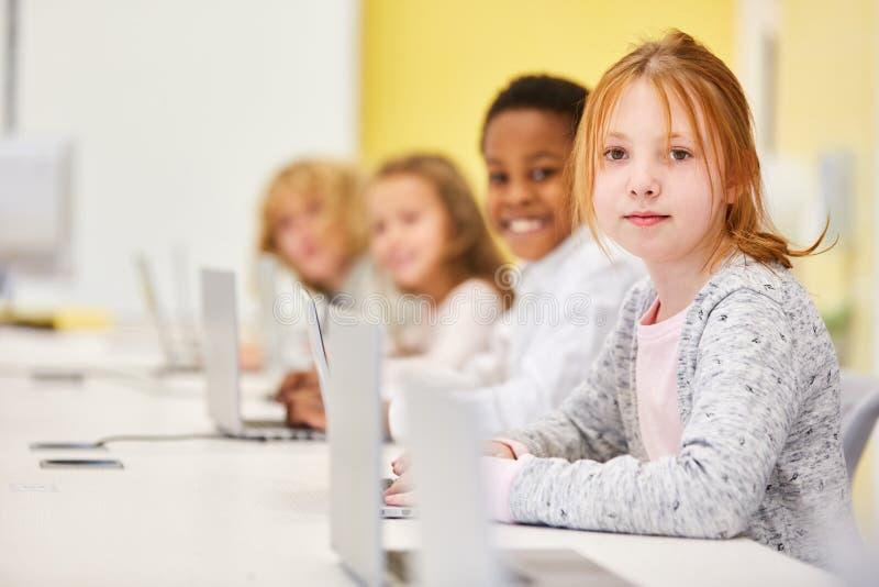 Ni?os en escuela primaria con el ordenador port?til foto de archivo