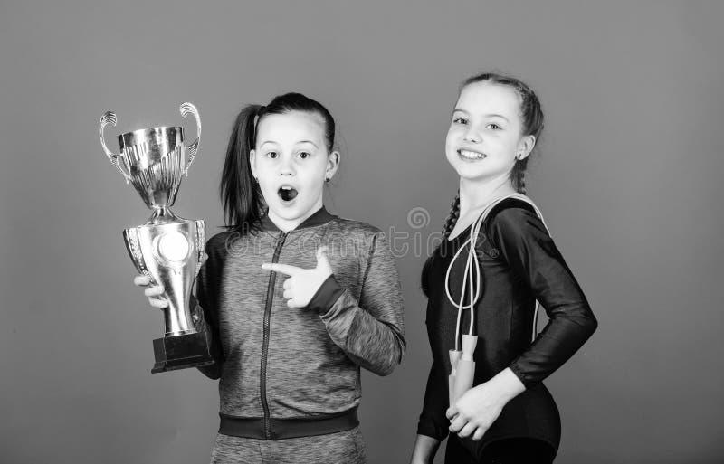 Ni?os felices con la taza de campe?n del oro La acrobacia y gimnasia Comba del control de las ni?as victoria de muchachas adolesc foto de archivo libre de regalías