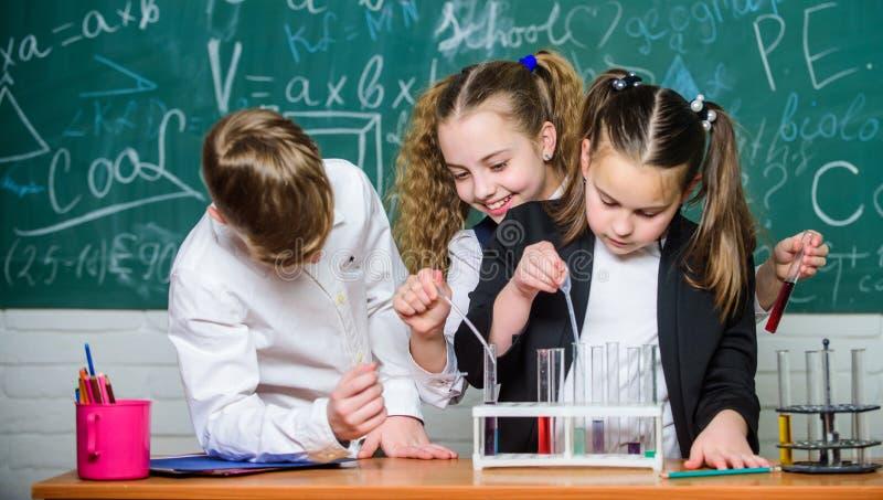 Ni?os felices Lecci?n de la qu?mica Ni?os que aprenden qu?mica estudiantes que hacen experimentos de la biología con el microscop imagen de archivo