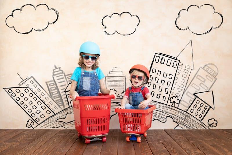 Ni?os felices que conducen el coche del juguete en casa fotografía de archivo libre de regalías