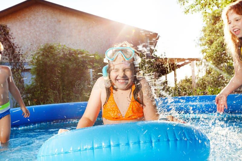 Ni?os felices que juegan en el agua azul de la piscina foto de archivo libre de regalías