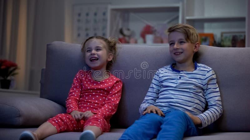 Ni?os felices que miran el sof? que se sienta de la pel?cula de la comedia, divirti?ndose, riendo junto imagenes de archivo