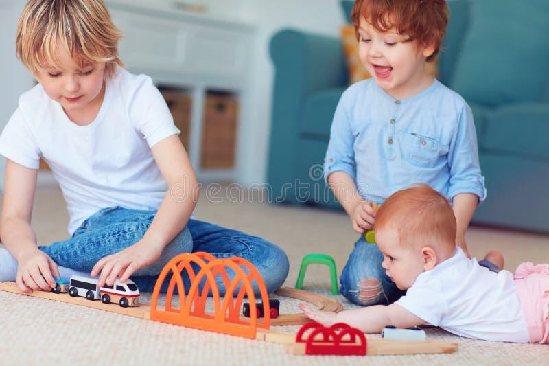 Ni?os lindos, hermanos que juegan los juguetes juntos en la alfombra en casa imagenes de archivo