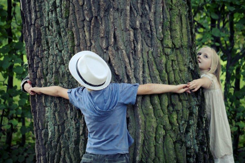 Ni?os que abrazan el ?rbol Naturaleza al aire libre de la protecci?n del medio ambiente Protecci?n al aire libre fotografía de archivo