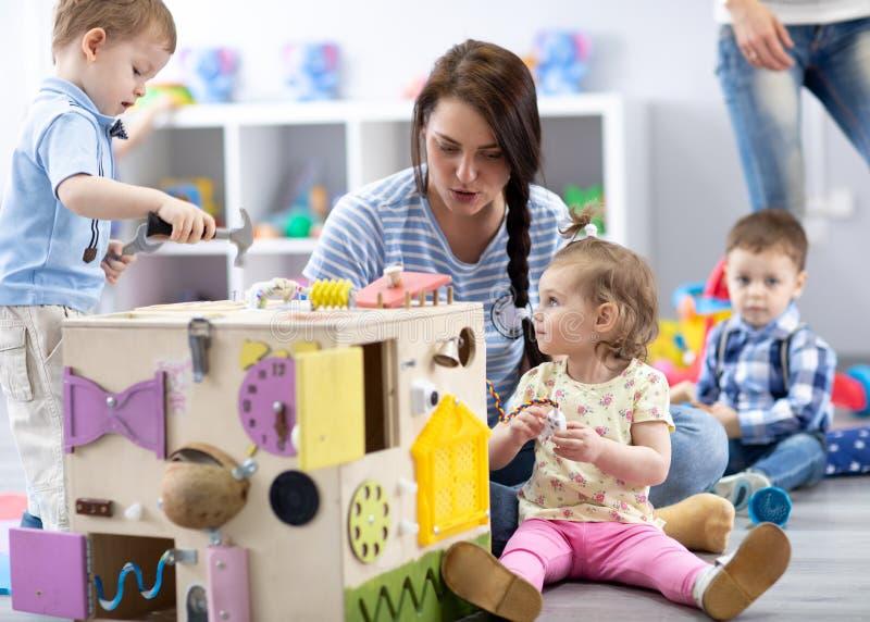 Ni?os que juegan con los juguetes educativos en cuarto de ni?os foto de archivo