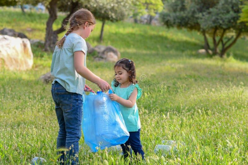 Ni?os que limpian en parque Ni?os voluntarios con un bolso de basura que limpia la litera, poniendo la botella pl?stica en el rec imagen de archivo