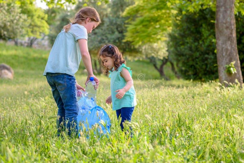 Ni?os que limpian en parque Ni?os voluntarios con un bolso de basura que limpia la litera, poniendo la botella pl?stica en el rec fotos de archivo