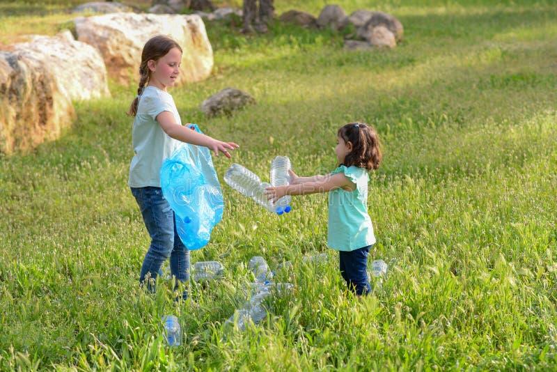 Ni?os que limpian en parque Ni?os voluntarios con un bolso de basura que limpia la litera, poniendo la botella pl?stica en el rec imágenes de archivo libres de regalías