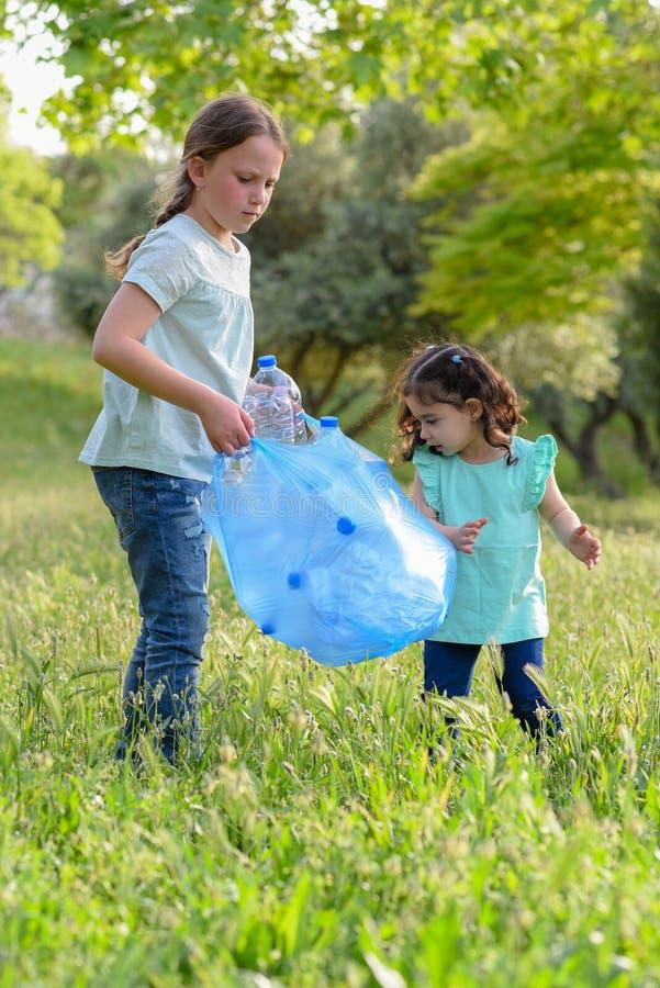 Ni?os que limpian en parque Ni?os voluntarios con un bolso de basura que limpia la litera, poniendo la botella pl?stica en el rec imagen de archivo libre de regalías