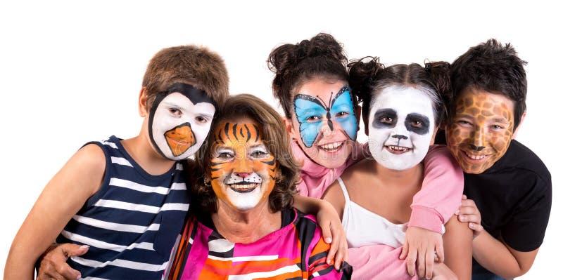 Ni?os y abuelita con la cara-pintura animal fotografía de archivo