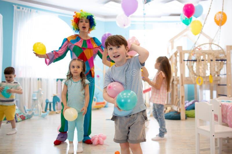 Ni?os y juego alegres del payaso con el globo del color en fiesta de cumplea?os fotos de archivo
