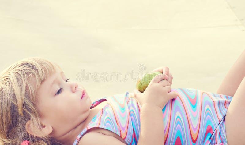 Ni?a peque?a adorable linda que come la pera fresca que miente en la playa imagenes de archivo