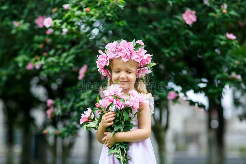 Ni?a sonriente linda con la guirnalda de la flor en el parque Retrato del peque?o ni?o adorable al aire libre midsummer D?a de ti imagen de archivo libre de regalías