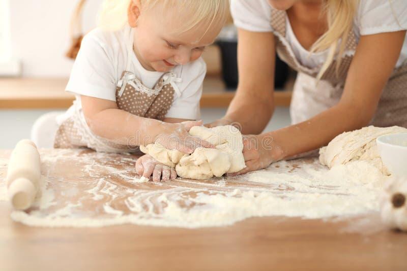 Ni?a y su mam? rubia en los delantales beige que juegan y que r?en mientras que amasa la pasta en cocina Pasteles hechos en casa fotos de archivo