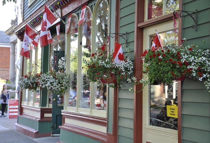 Niagara auf dem See, am 25. Juni: Speichern Sie Eingang und kanadisches Flaggen herein Stadtzentrum von Niagara-auf-d-See von Ont stockbilder
