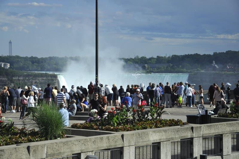 Niagara Falls, el 24 de junio: Turistas que miran las cascadas de Niagara Falls del lado canadiense fotos de archivo libres de regalías