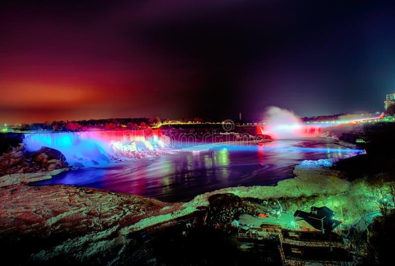 Niagara Falls iluminou-se na noite por luzes coloridas imagens de stock