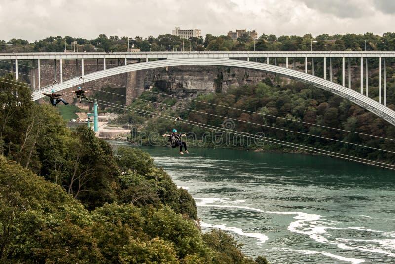 Niagra cai Canadá 06 09 2017 povos que usam ziplining extremo da atração de Zipline sobre as cachoeiras foto de stock royalty free