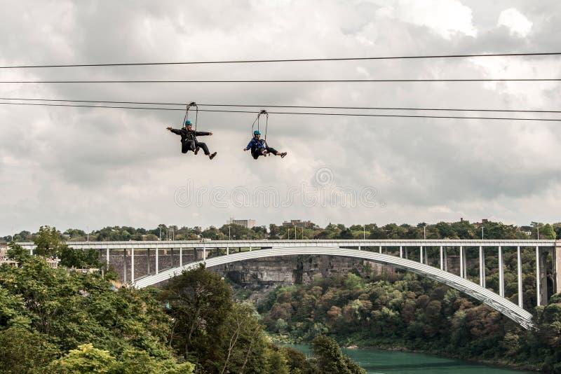 Niagra cai Canadá 06 09 2017 povos que usam ziplining extremo da atração de Zipline sobre as cachoeiras fotos de stock
