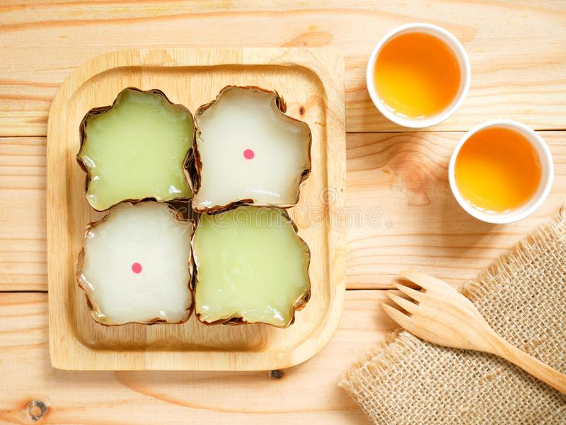 Nian gao or Chinese New Year`s cake rice cake. Nian gao, nin gou or Chinese New Year`s cake rice cake made from glutinous rice flour served with cups of tea stock photo