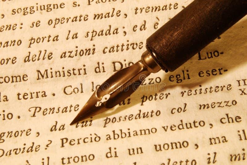 Nib (pen) over an old book. Wooden nib over an very old book royalty free stock photos