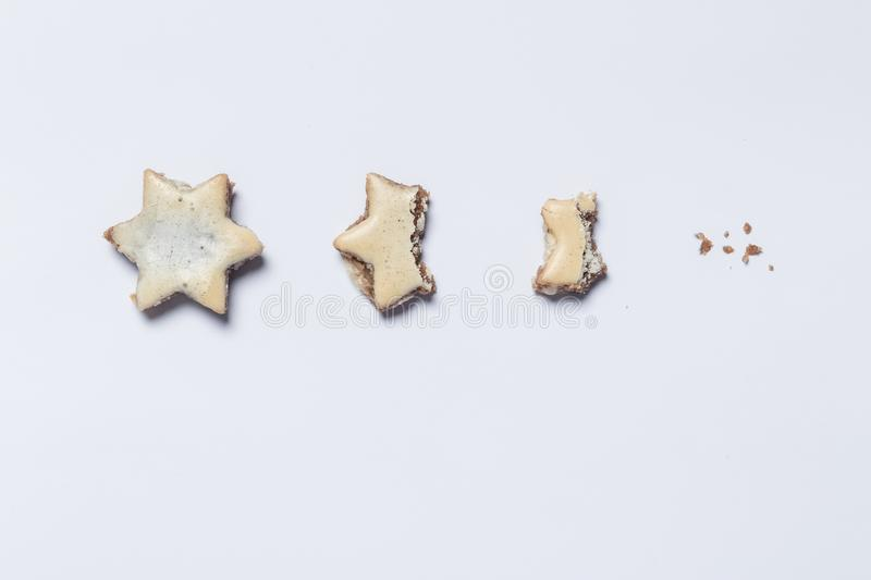 Nibbled off cinnamon stars on white background as symbol of the stock images