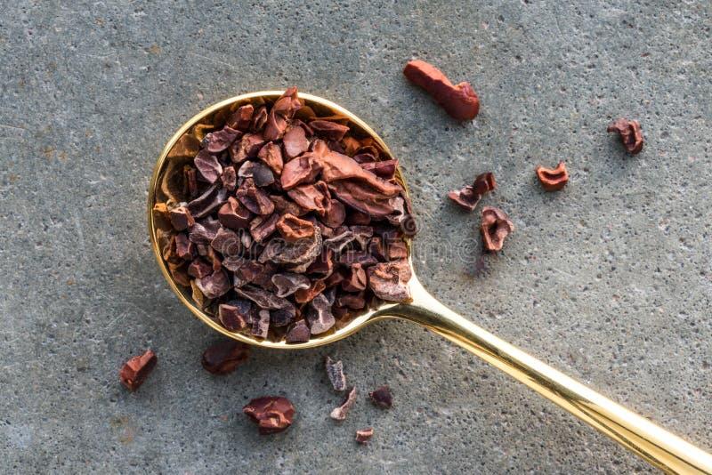 Nibs какао на ложке золота стоковые изображения