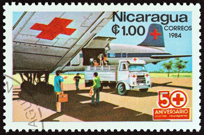 NICARAGUA - CIRCA 1984: En stämpel som skrivs ut i Nicaragua Röda korsetflygplan och ambulans, circa 1984 royaltyfri bild