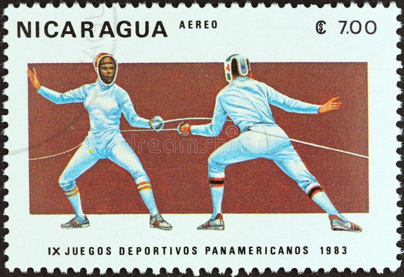 NICARAGUA - CIRCA 1983: A stamp printed in Nicaragua shows fencing, circa 1983. NICARAGUA - CIRCA 1983: A stamp printed in Nicaragua from the `9th Pan American royalty free stock photo