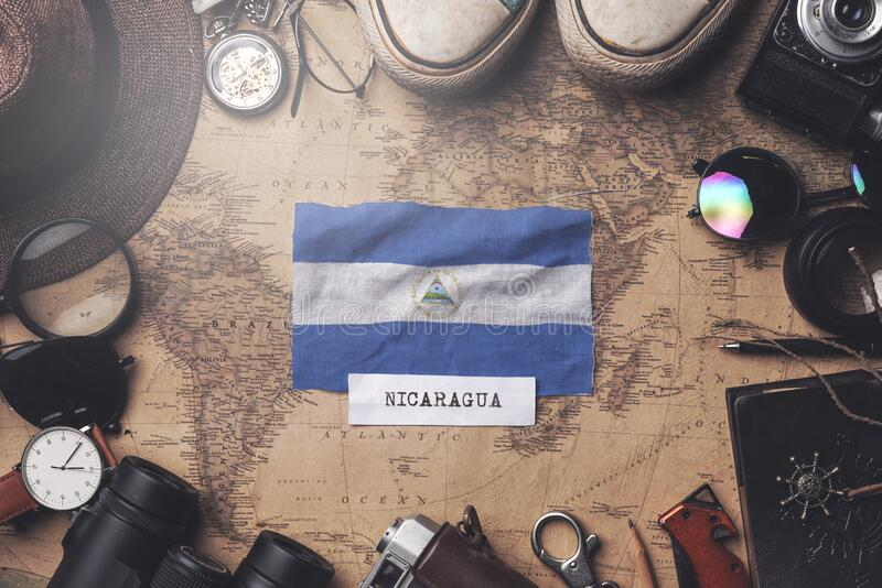 Nicaragua Flag Between Traveler`s Accessories on Old Vintage Map. Overhead Shot.  royalty free stock images