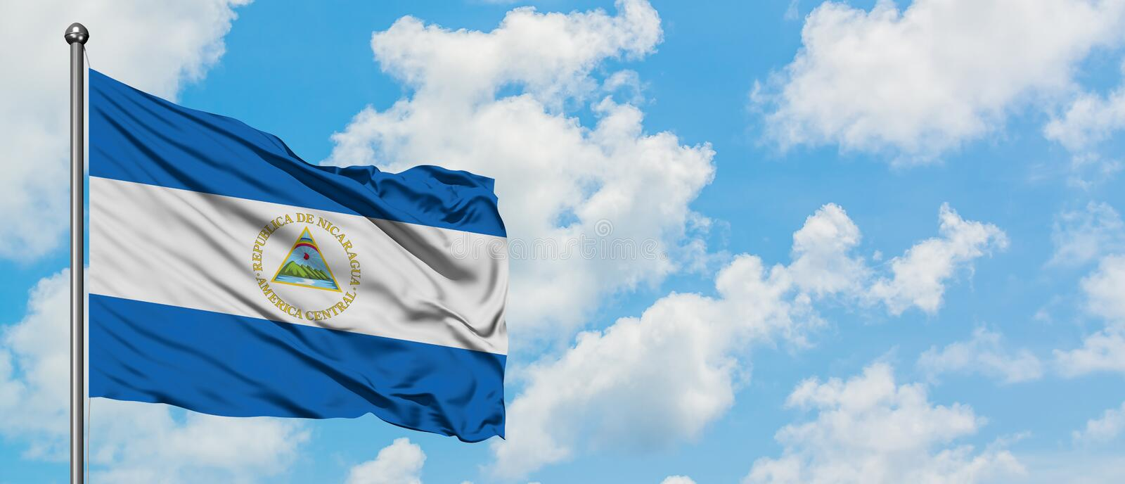 Nicaragua flag waving in the wind against white cloudy blue sky. Diplomacy concept, international relations.  royalty free stock photo