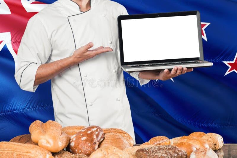 Nicaraguan Baker holdingslaptop op de vlag van Nicaragua en brodenachtergrond Chef-kok die het eenvormige het richten lege scherm stock fotografie
