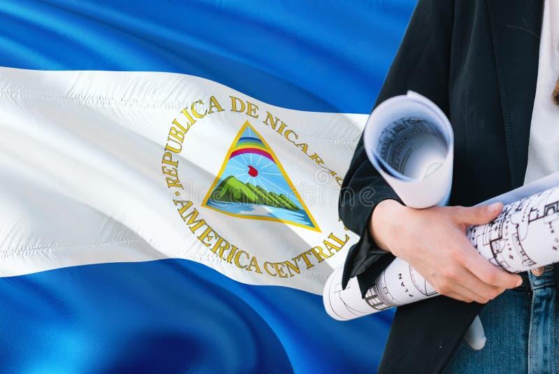 Nicaraguan de holdingsblauwdruk van de Architectenvrouw tegen golvende de vlagachtergrond van Nicaragua Bouw en architectuurconce stock fotografie