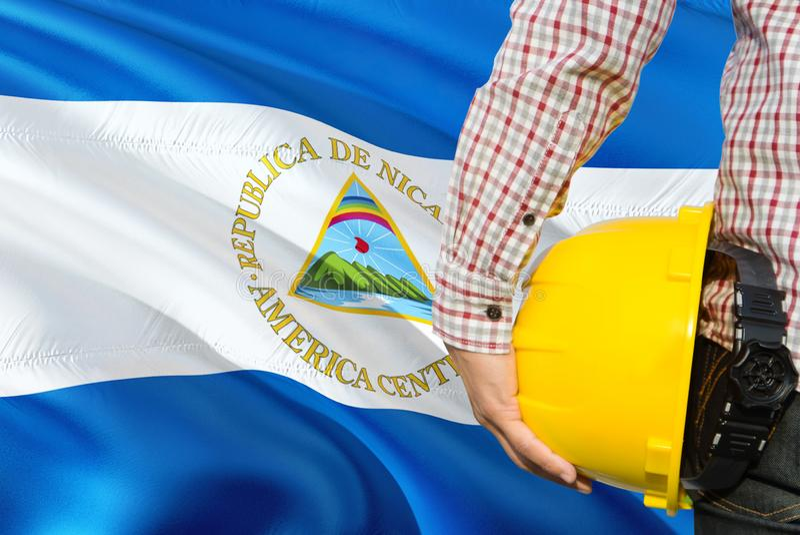 Nicaraguan Ingenieur houdt gele veiligheidshelm met golvende de vlagachtergrond van Nicaragua Bouw en de bouwconcept royalty-vrije stock afbeeldingen