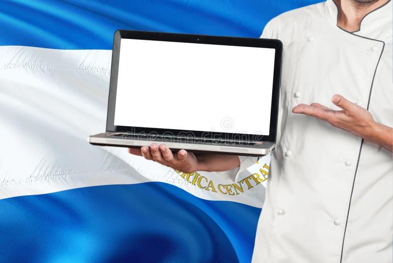 Nicaraguan laptop van de Chef-kokholding met het lege scherm op de vlagachtergrond van Nicaragua Kok eenvormig dragen en het rich royalty-vrije stock fotografie