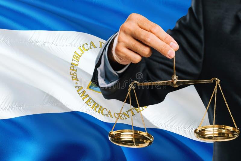 Nicaraguan Rechter houdt gouden schalen van rechtvaardigheid met golvende de vlagachtergrond van Nicaragua Gelijkheidsthema en ju royalty-vrije stock afbeelding