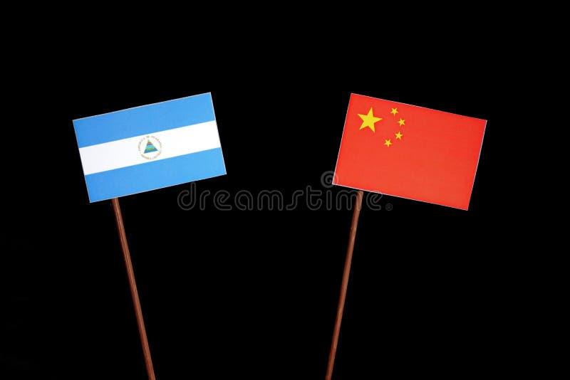 Nicaraguan vlag met Chinese vlag op zwarte stock afbeeldingen