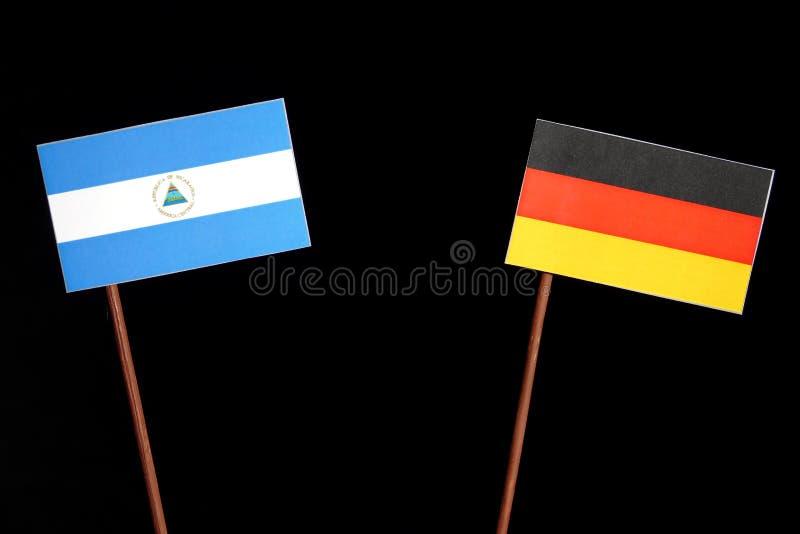 Nicaraguan vlag met Duitse vlag op zwarte stock foto's