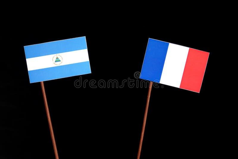 Nicaraguan vlag met Franse vlag op zwarte stock afbeeldingen